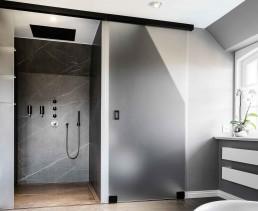 Die großzügige Dusche und das Dusch-WC mit gemeinsamer Front und blickdichter Glasschiebetür