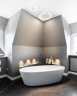 Die freistehende Badewanne ist eingebettet in einen Dachgiebel