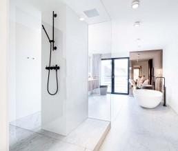 """Großzügige Dusche in hellem Bad mit Naturstein von Salvatori, Duschkopf in der Decke von Dornbracht """"Big Rain"""""""