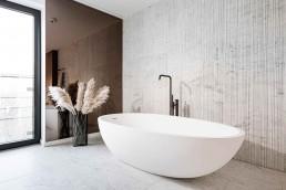 Reliefnaturstein Salvatori, frei stehende Badewanne von Agape, Standarmatur Vola mit Handbrause
